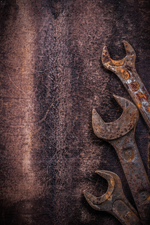 obsolete: Obsolete spanner wrenches on vintage leather construction concept.