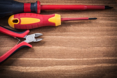 insulated: Insulated screwdrivers nippers on wooden board top view electricity concept.