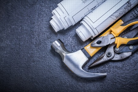 architectural building: Rolled blueprints steel cutter pliers claw hammer on black background. Stock Photo
