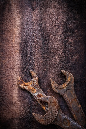 close up  wrench: Rusted hook wrenches on vintage leather construction concept. Stock Photo
