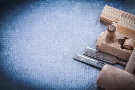 chisels: Wooden planer hammer bricks firmer chisels on metallic background copyspace.