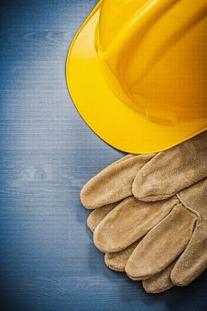hard hat: Safety gloves hard hat on wooden board construction concept.