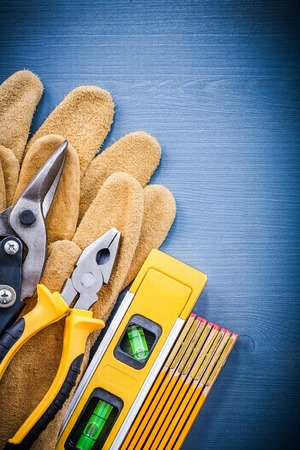 snips: Pliers sharp tin snips wooden meter construction level protective gloves. Stock Photo
