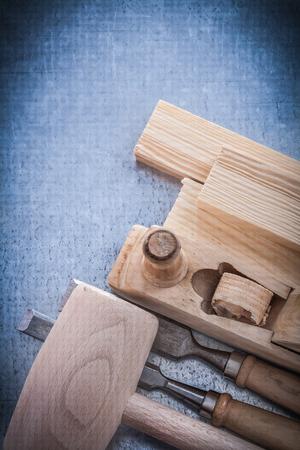 chisels: Wooden planer hammer bricks flat chisels on metallic background.