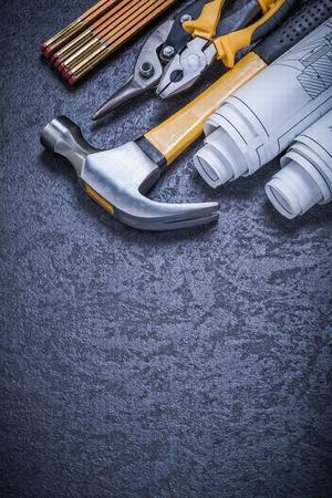 blueprint: Rolled blueprints steel cutter gripping tongs claw hammer wooden meter.