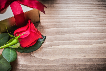 expanded: Present box with tied bow natural rose on wooden board. Stock Photo