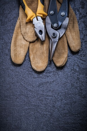 gripping: Steel cutter gripping tongs leather safety glove on black background. Stock Photo