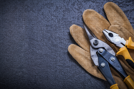snips: Sharp tin snips pliers leather safety glove construction concept.