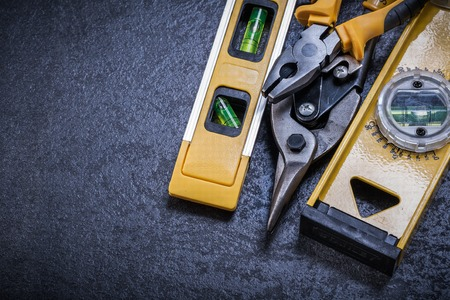 construction level: Tin snips pliers construction level on black background.