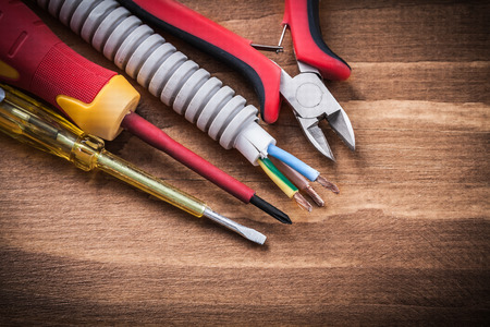 insulated: Nippers insulated screwdrivers corrugated pipe on wooden board. Stock Photo