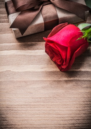 expanded: Boxed present expanded rosebud on wooden board holiday concept.