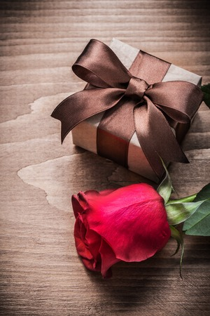 expanded: Present box expanded red rose on wooden board holiday concept.