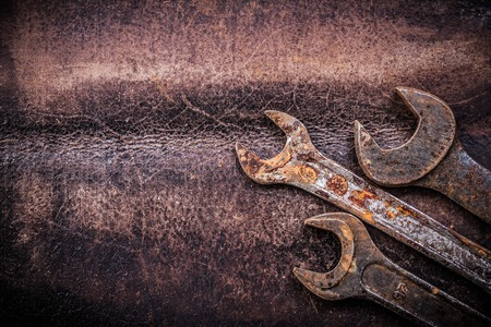 close up  wrench: Rusty spanner wrenches on vintage leather construction concept.