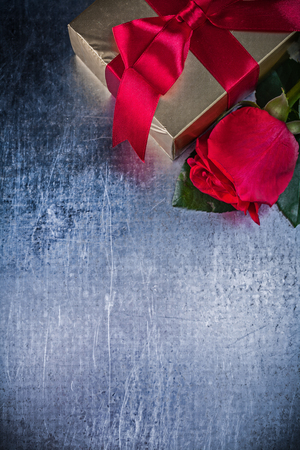 expanded: Composition of natural rose present box on scratched metallic background.