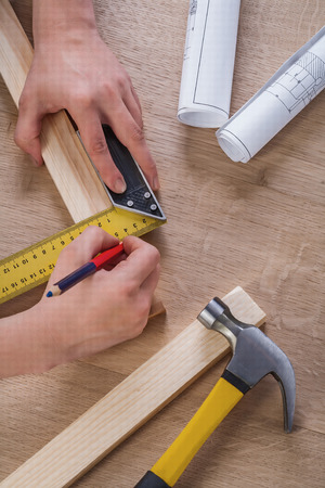 square ruler: hands of joiner in work with pencil and square ruler. Stock Photo