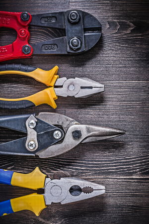 snips: Collection of tin snips steel cutter pliers on wooden board.
