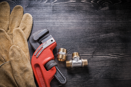 protective gloves: Adjustable wrench plumbing fixtures protective gloves on wooden board.