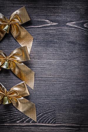 festal: Festal golden bows with bells on wood board holiday concept.
