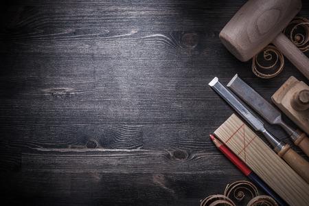 wood planer: Flat chisels planer wood shavings pencil wooden plank mallet copyspace.