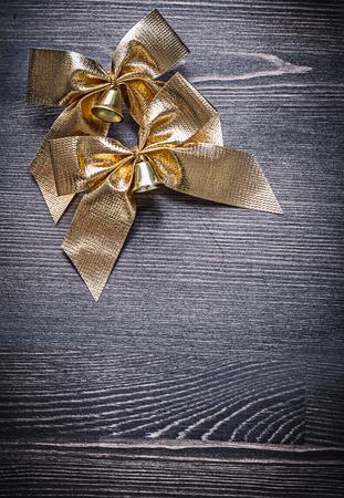 festal: Christmas festal golden bows on wooden board holiday concept.