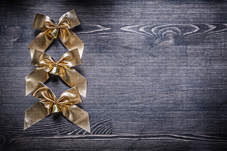 goldish: Christmas festal goldish bows on wooden board holiday concept.