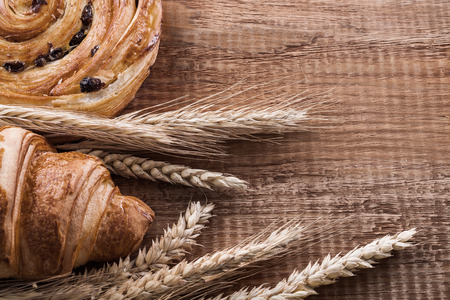 oaken: Golden wheat ears roll with raisins baked croissant on oaken wooden board food and drink concept.