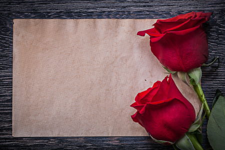 invitation cards: Blank vintage paper red natural roses on wooden board. Stock Photo