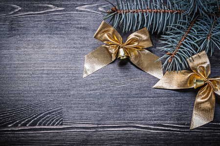 goldish: Goldish bows fir tree branch on wooden board holiday concept.