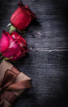 moños navideños: capullos de rosa perfumados florecido envasados ??en caja de regalo de madera concepto de vacaciones de fondo. Foto de archivo