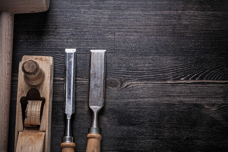 chisels: Collection of wooden mallet chisels shaving plane on wood board.