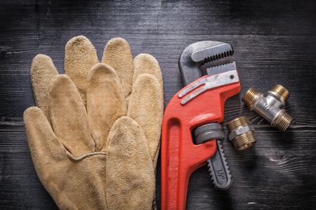household fixture: Adjustable wrench plumbing fittings leather protective gloves on wooden board.