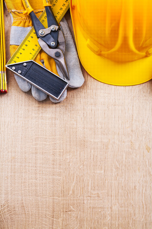 square ruler: Hard hat protective glove square ruler wooden meter nippers on oak board construction concept