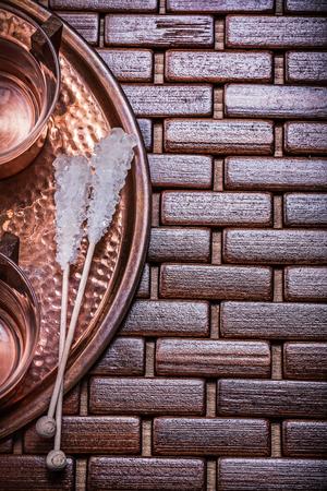 matting: Copper tray tea cups sugar sticks on wooden matting. Stock Photo
