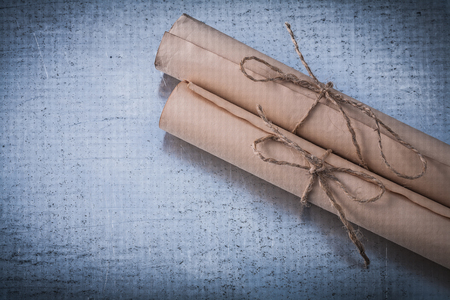 corded: Age-old corded paper rolls on scratched metallic surface. Stock Photo