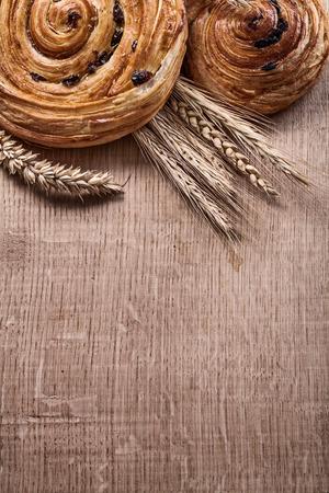oaken: Golden wheat ears raisin baked buns on oaken wooden board food and drink concept. Stock Photo