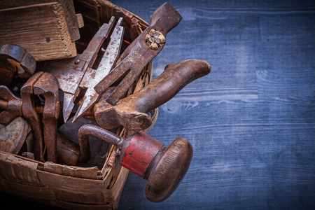 box construction: Collection of vintage rough tools in wicker box construction concept.