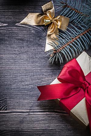 giftbox: Christmas bow fir branch giftbox on wood board holiday concept. Stock Photo