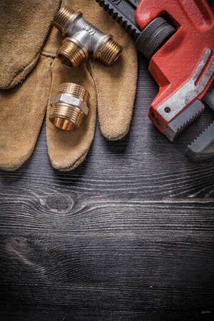 household fixture: Adjustable wrench connector fittings safety gloves on wooden board.