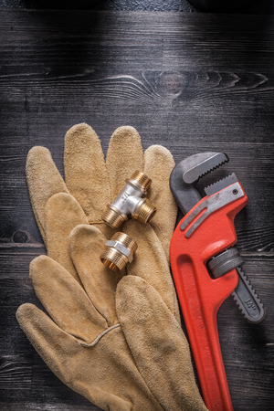 household fixture: Adjustable wrench plumbing fittings leather safety gloves on wood board.