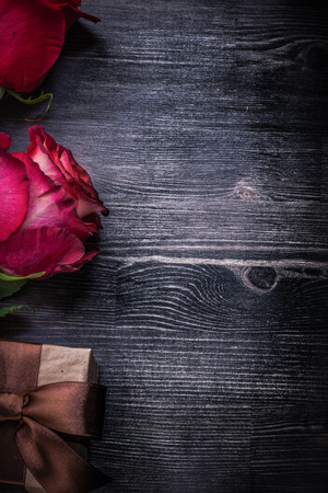 packed: Composition of bloomed scented rosebuds packed giftbox on wooden background.