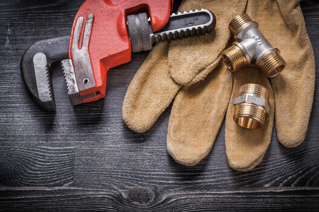 protective gloves: Adjustable wrench connector fittings protective gloves on wooden board.