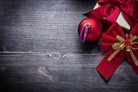 giftbox: Christmas shining ball bow giftbox on wooden board.