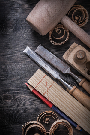 wood planer: Firmer chisels planer wood shavings pencil wooden plank mallet. Stock Photo