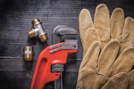 protective gloves: Adjustable wrench plumbing fittings protective gloves on wooden board.