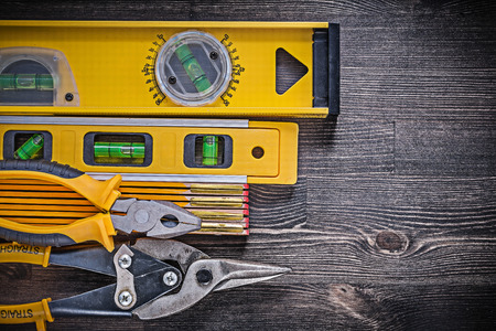 snips: Construction level wooden meter pliers tin snips on wooden background.
