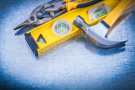 construction level: Construction level claw hammer tin snips on metallic background. Stock Photo