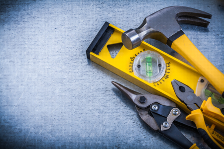 snips: Construction level claw hammer tin snips pliers on metallic background.