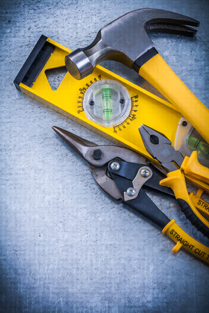 construction level: Construction level claw hammer steel cutter pliers on metallic background.