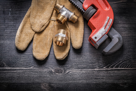 household fixture: Adjustable wrench pipe fittings safety gloves on wooden board.