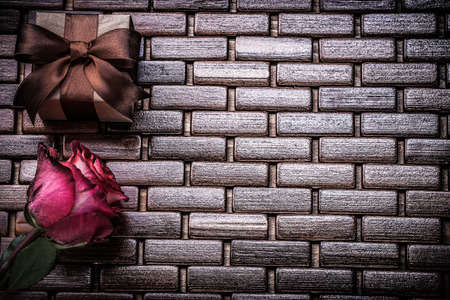 matting: Red scented rose giftbox on wicker wooden place matting.